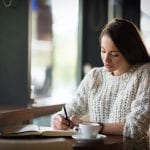 Beautiful woman sitting in restaurant and writing
