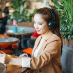 Young smiling asian girl student in headphones communicates by tablet at cafe